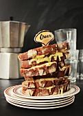 A stack of melted cheese rye bread sandwiches in a retro diner setting