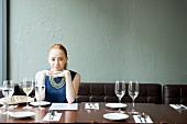 Junge Frau mit blauem Kleid in einem Restaurant sitzend