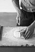 Mid adult baker slicing fresh dough