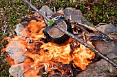 Kettle with coffee over campfire