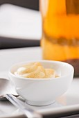 Closeup of dijon mustard in a white bowl and a spoon. A bottle of vinegar in the background.