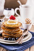 Stack of pancakes with cream, blueberry and raspberry