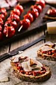 Bruschetta and grilled spicy tomato on a wooden cutting board.