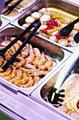 Marinated prawns and vegetables on display in the counter at a delicatessen
