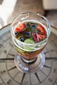 A berry & cucumber drink in a glass