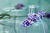 A sprig of lavender on a bottle of scented oil