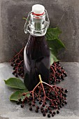 A bottle of elderberry juice and fresh elderberries
