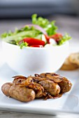 Fried sausages with onions and salad