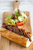 Baguette filled with fried sausage and onions