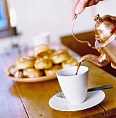 Coffee being poured into a cup from a copper pot