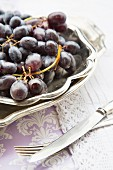 Red grapes in a silver dish with silver cutler to one side