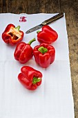 Red peppers on a tea towel with a knife