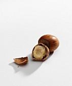 A whole hazelnut and one broken open