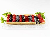 A Rectangular Mixed Berry Fruit Tart on a Glass Tray Garnished with Mint Leaves