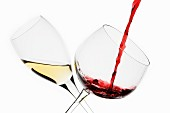 A Glass of White Wine and a Glass of Red Wine being Poured