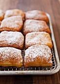 Beignets Freshly Dusted with Powdered Sugar resting on a Wire Rack