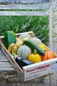 A wooden crate of vegetables and melons