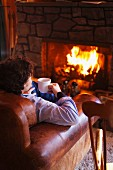 Man next to fire with cup of hot drink