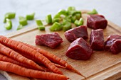 Chunks of Raw Beef, Raw Carrots and Chopped Celery on a Wooden Cutting Board