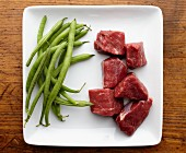 Raw Chunks of Beef and String Beans on a White Plate from Overhead