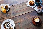 Breakfast scene overhead - Granola, blueberries, yogurt, orange juice, coffee, doughnuts, croissants, muffins