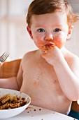 Kleiner Junge isst Fusilli Bolognese