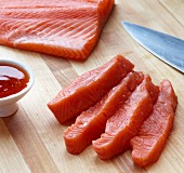 Pieces of Freshly Cut Salmon Steak on a Wooden Board with a Little Bowl of Chili Sauce