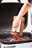 Pouring Hot Coals onto Barbecue