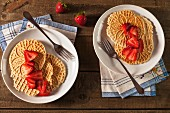 Two Plates of Pizzelles with Sliced Strawberries