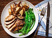 Sliced Grilled Chicken, Broccolini and Roasted Potatoes with Thyme on a White Plate set on a Wood Table with a Blue Plaid Napkin