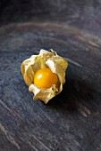 A Cape gooseberry on a wooden surface