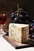 A wedge of blue cheese with grapes and red wine