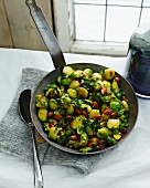 Frying pan with organic brussel sprouts, herbs and nuts