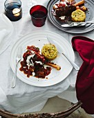 Dining table with plates of lamb shank and potato rosti
