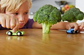 Boy playing cars around broccoli trees
