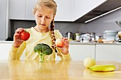 Mädchen balanciert Apfel und Tomate auf einer Brokkoli-Waage