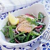 Fried fish fillet on mange tout salad with red onions