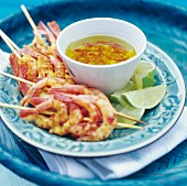 Prawn skewers with chilli sauce and limes