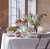 A table laid for tea, with meringues, grapes and a bunch of lilacs