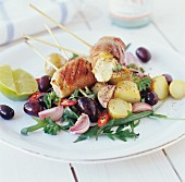 Fish skewers with bacon on potato & olive salad