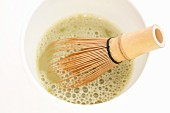 Matcha tea in a bowl with a tea whisk (close-up)