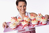 A woman holding a tray of cupcakes topped with letters reading 'Merry Xmas'