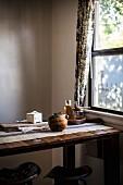 Ein Eichelkürbis auf rustikalem Tisch vor Fenster
