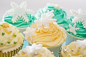 Cupcakes decorated with a winter theme, with yellow and green icing