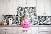Mädchen mit pinkfarbenem Ballettkleid auf Stuhl vor der Küchenspüle