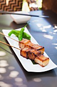 Skewers of Pork Belly on a White Plate