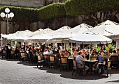 Street café with sun shades and lots of guests