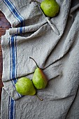 Three pears and a knife on a linen cloth