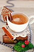 A cup of coffee with a mini gingerbread house for Christmas
