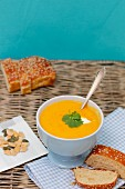 Pumpkin soup with coriander leaves, pumpkin seeds and sesame seed bread